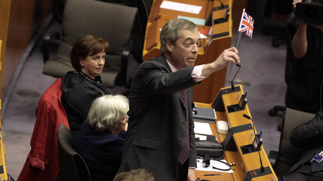 Nigel Farage waves a Union flag as he leaves the chamber in Brussels