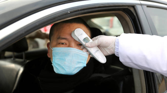 Chinese citizens are temperature checked at checkpoints