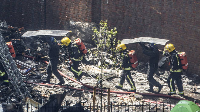 Riot police protect firefighters from falling debris
