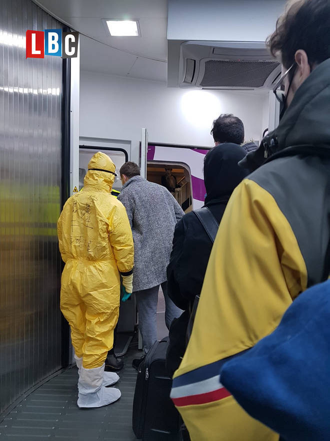 Passengers were greeted by staff in hazmat suits on their chartered flight back to the UK