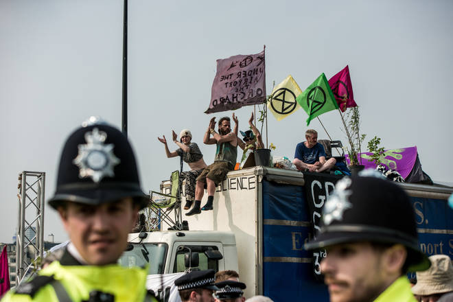 Police stand and watch as Extinction Rebellion protesters block a road in London