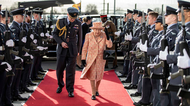 Queen Elizabeth II is escorted past an RAF guard of honour as she arrives for a visit to Royal Air Force Marham