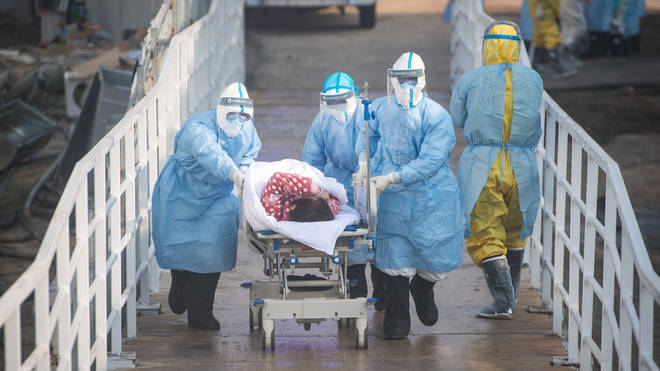 Medical workers help the first batch of patients infected with the novel coronavirus move into their isolation wards at Huoshenshan Hospital in Wuhan