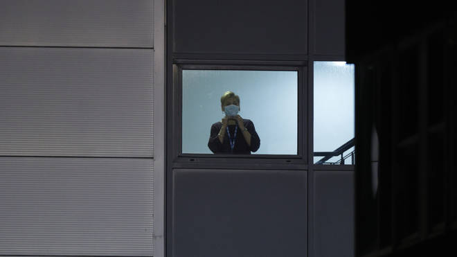 A nurse looks out from a window at Arrowe Park