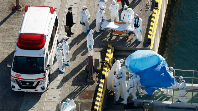 An infected passenger is lead from the ship in Japan