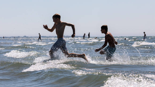 Two boys play in the sea during the hot weather