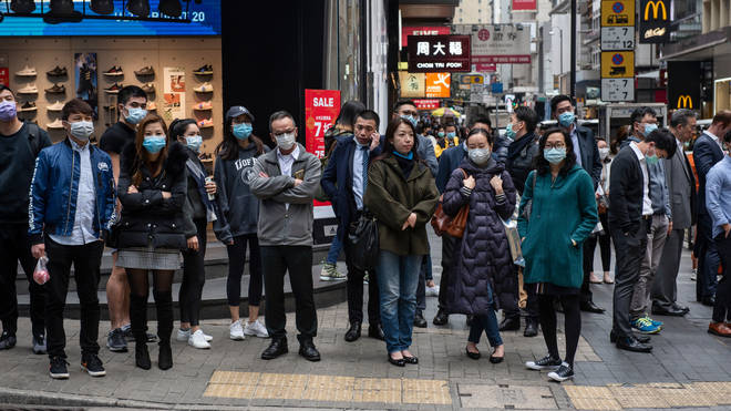 Pedestrians wearing face masks wait at a traffic light in Central district, Hong Kong