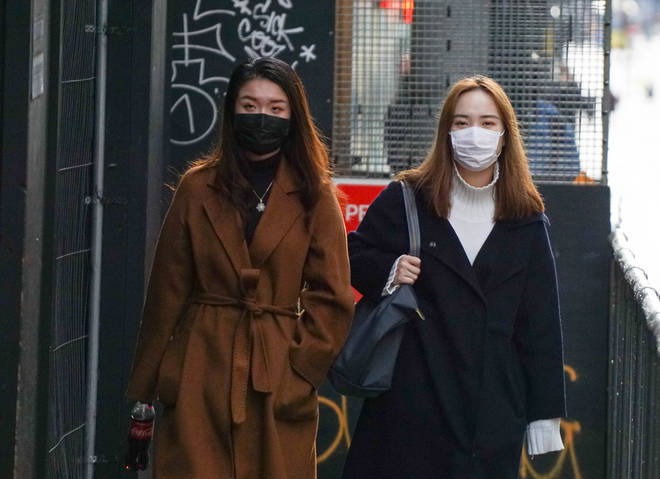 Two women wear face masks on a street in Manchester