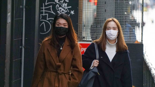 Two women wear face masks in a street in Manchester