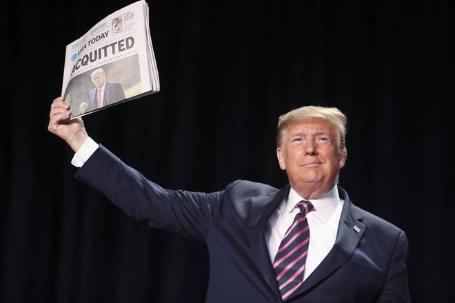 Mr Trump held up newspapers with the headlines 'Acquitted'