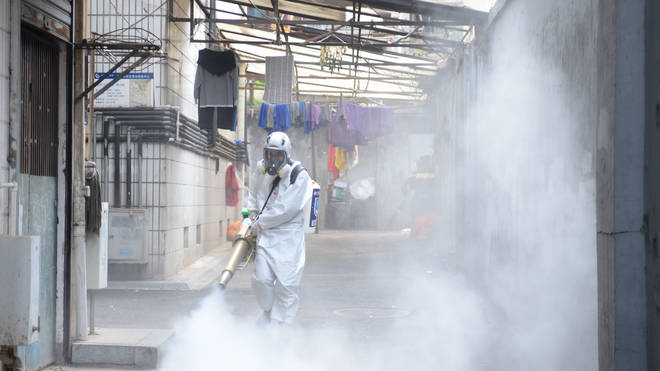 A worker disinfects an area in China
