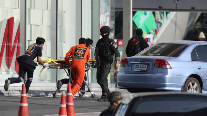 Medics carry a stretcher towards Terminal 21 Korat mall