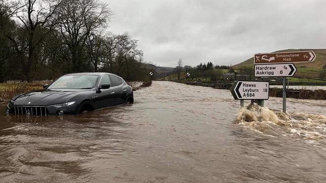 Cars struggle in deep flood waters near Appersett, North Yorkshire
