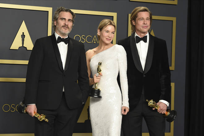 He poses with fellow winners Renee Zellweger and Brad Pitt