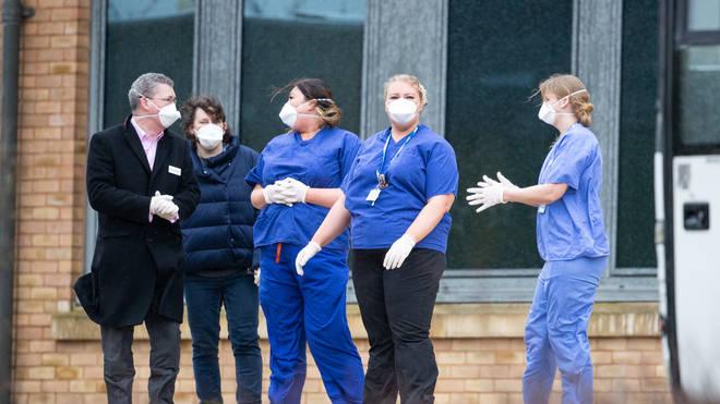 Nursing staff wait to greet people heading into quarantine in the UK