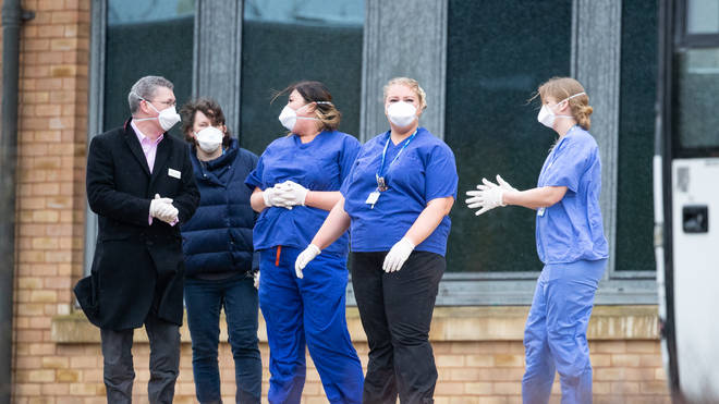 Medical staff wait to greet people heading into quarantine in the UK