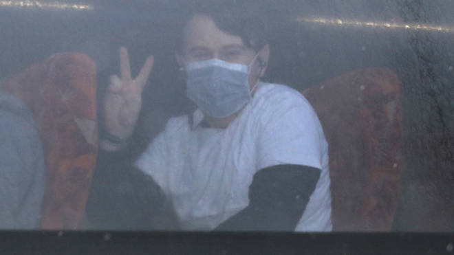 A passenger gives a peace sign as coaches carrying Coronavirus evacuees arrive at Kents Hill Park Training and Conference Centre, in Milton Keynes,