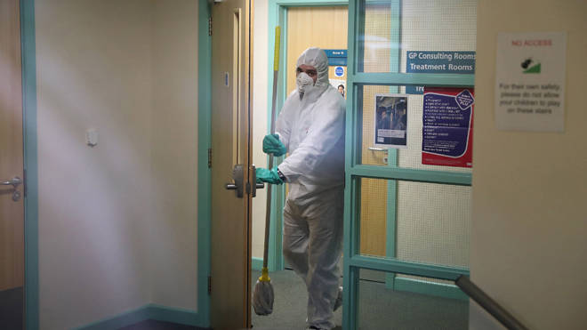 A man in protective clothing cleaning the County Oak Medical Centre GP practice in Brighton