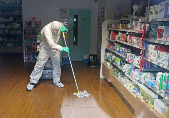 A cleaner in a hazmat suit disinfects a pharmacy in Brighton
