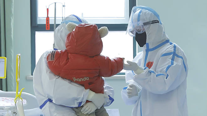 Medical staff tend to a baby infected with coronavirus