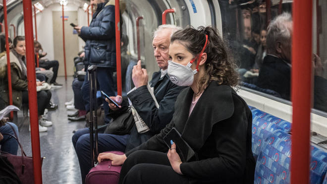 A woman seen on a tube wearing a face mask. A total of nine people in the UK are now being treated for COVID-19