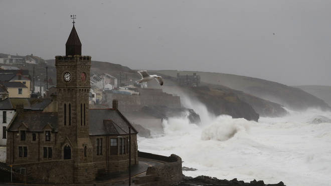 Powerful waves break on the shoreline around the small port of Porthleven, south west England
