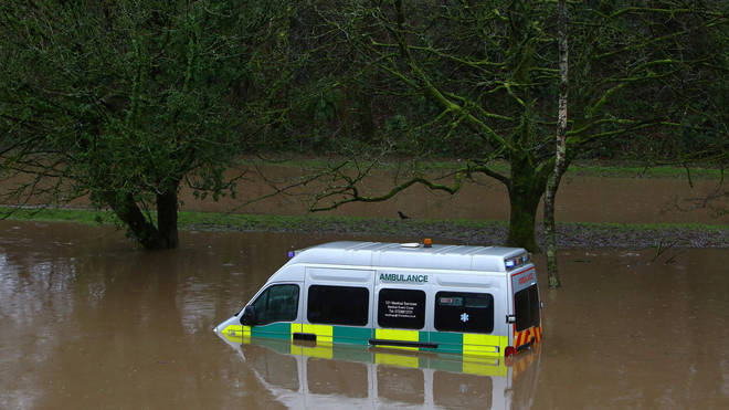 An Ambulance stands submerged in flood water after the River Taff burst its banks in Nantgarw, south of Ponypridd in south Wales