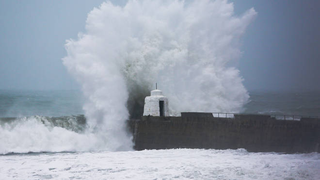 Waves pound against the harbour wall at Portreath, Cornwall