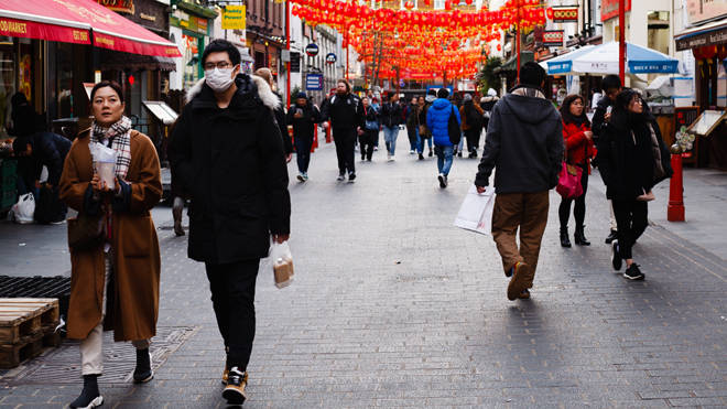 People wear medical face masks on Gerrard Street in Chinatown in London (file image)