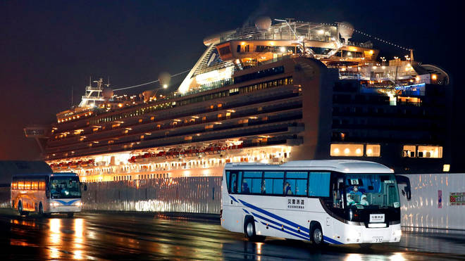 Buses carrying US passengers who were aboard the quarantined cruise ship leave the port