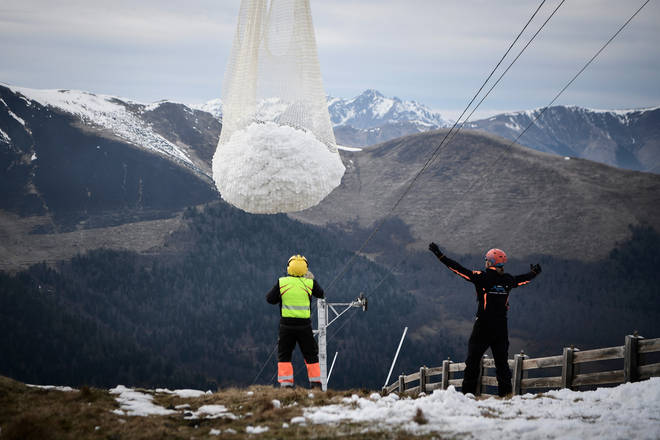 Workers were seen delivering snow to the slopes