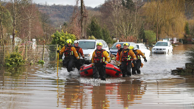 A care home resident is pulled to safety by rescue workers as floodwater surrounds the village of Whitchurch in Herefordshire