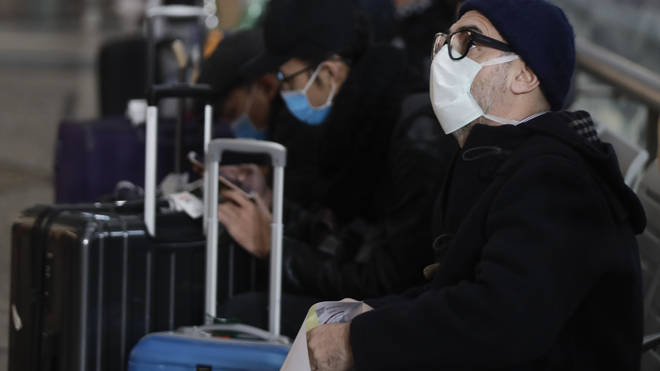 People wearing sanitary masks sit as they wait at the Centrale main railway station in Milan