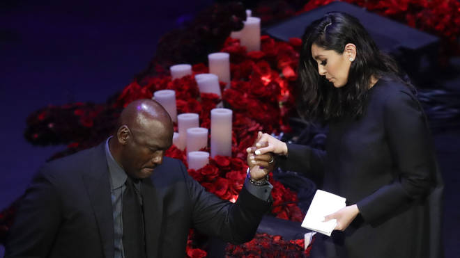Vanessa is helped down from the stage by Michael Jordan