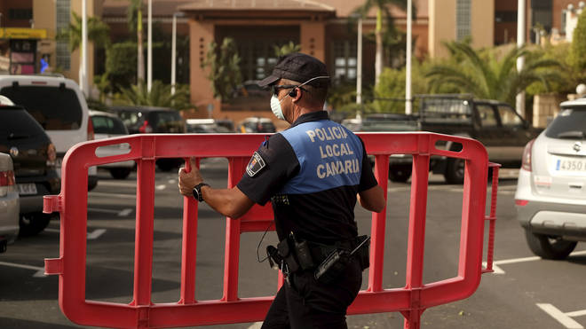 A Spanish police officer sets a barrier blocking the access to the H10 Costa Adeje Palace hotel