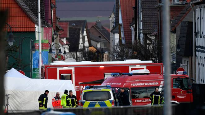 Vehicles of the police and the fire brigades stand at the site where a man who drove into a carnival procession