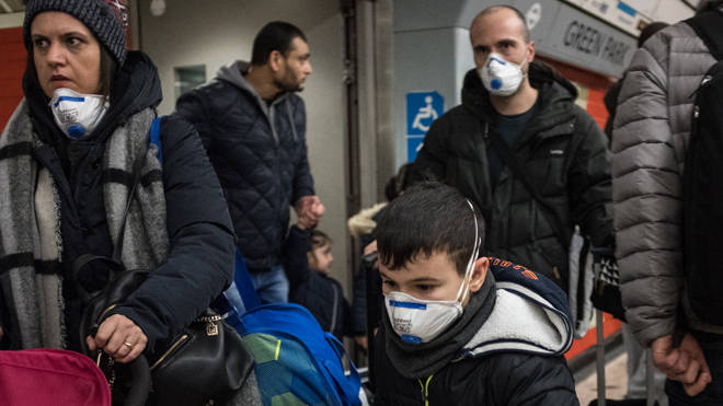 People are seen on a tube wearing face masks