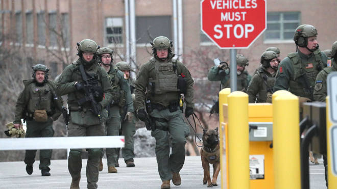 Tactical police teams sweep the grounds after the shooting