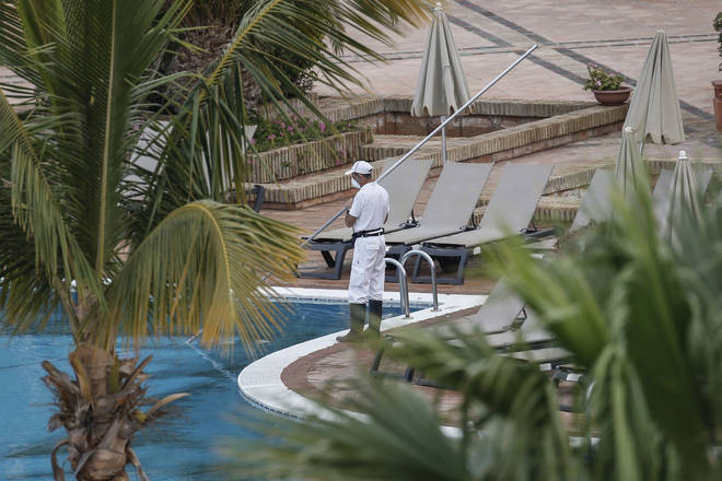 A cleaner cleans the pool at the hotel
