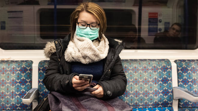 A woman wears a mask on the tube in London