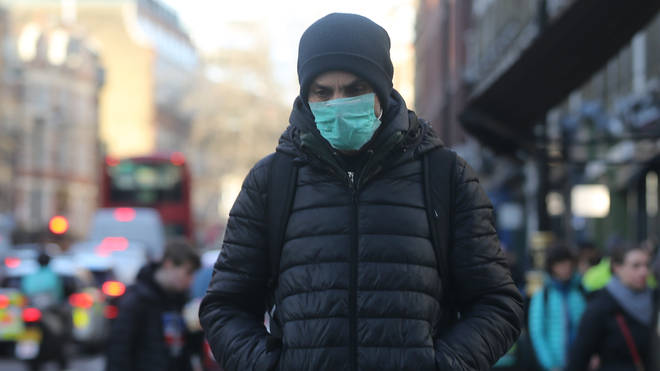 A man walks in a protective mask in London
