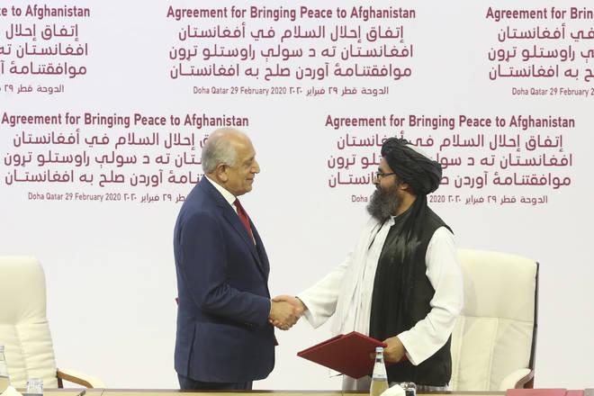 U.S. peace envoy Zalmay Khalilzad, left, and Mullah Abdul Ghani Baradar, the Taliban group's top political leader