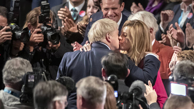 Boris Johnson and Carrie Symonds share a kiss after the Tory election victory