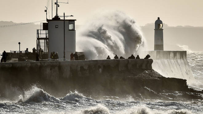 People watch as huge waves hit the sea wall in Porthcawl, South Wales