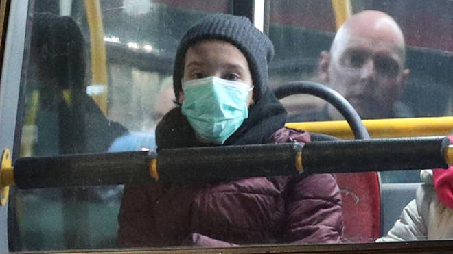 A woman in a face mask on a London bus