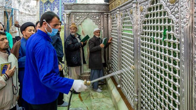 A man disinfects the shrine of Saint Masoumeh against coronavirus