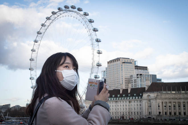 A woman wears a facemask to protect herself in London