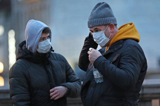 People wearing facemasks in Trafalgar Square over coronavirus fears