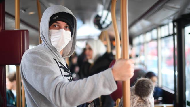 A man wears a mask on board public transport in London