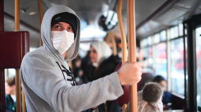 A man wears a mask on board public transport in London.